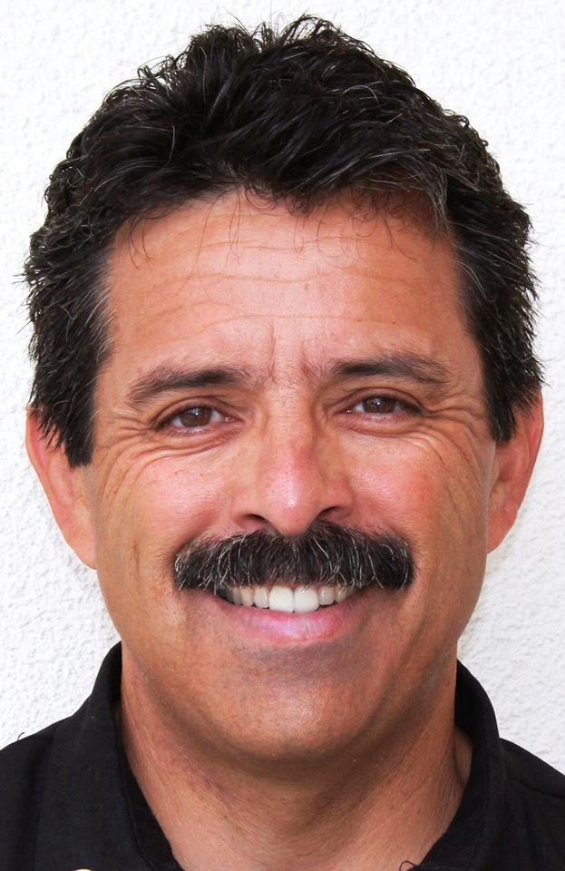 Color head shot of Fire Chief Ralph Terrazas. Smiling Latino with dark hair and mustache.