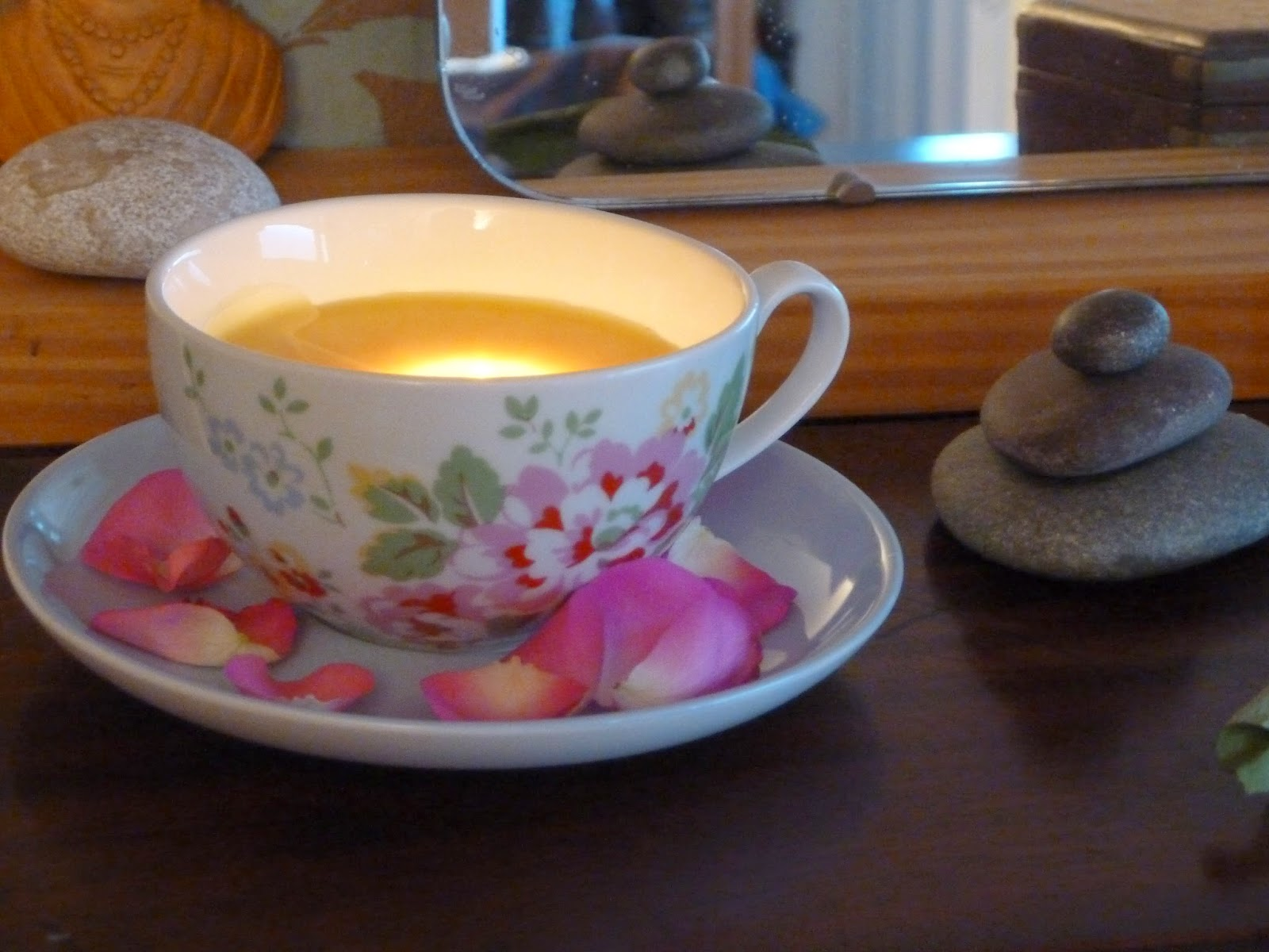 Beeswax candle in teacup with rose petals
