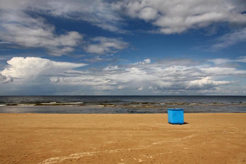 Praia deserta com céu azul mas com nuvens. No areal uma caixa grande pintada de azul