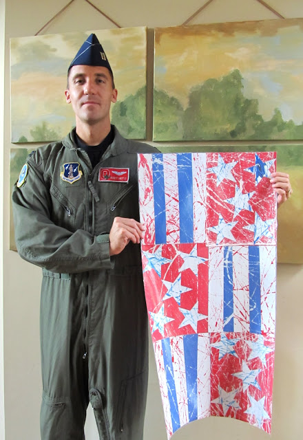 "photo of: Captain Mettle displays Kindergarten Artwork inspired by ""Red, White and Blue"" picture book"