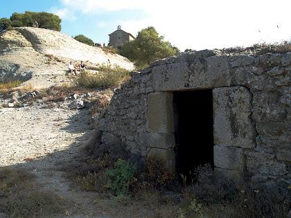 La cisterna del mas Barnils amb l'ermita de la Mare de Déu del Roser al fons