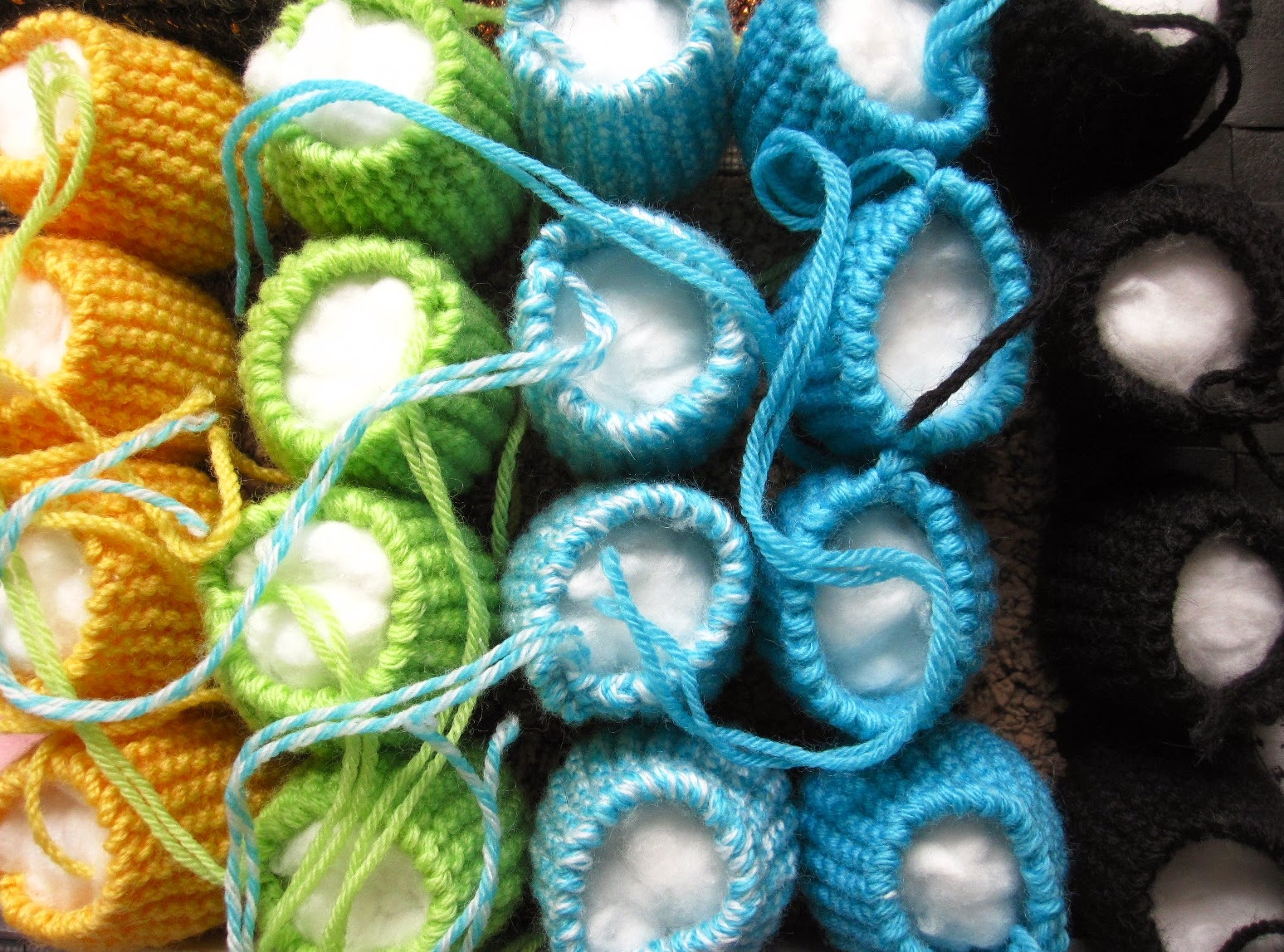 Rows of modern dolls' house miniature knitted pouffes, stuffed and awaiting sewing the tops.