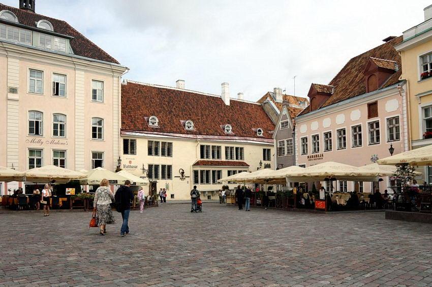 Foto de um canto da praça com os edifícios muito bem conservados e esplanadas em frente destes