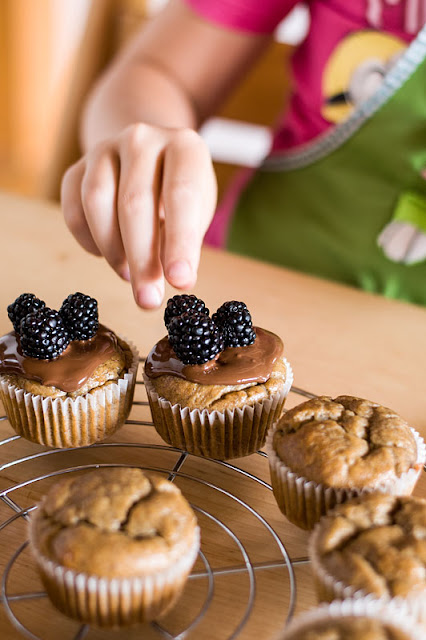 Vegan banana muffins covering with chocolate and adding blackberrys