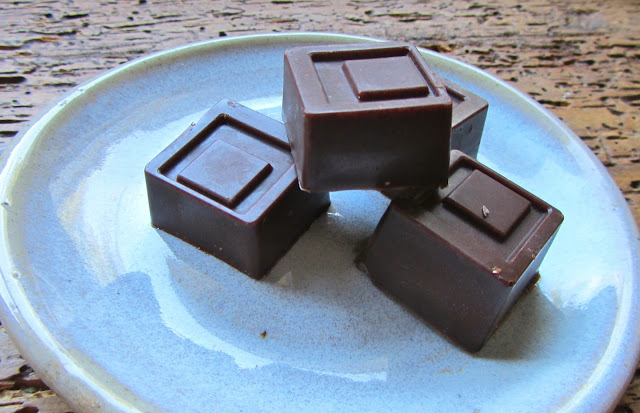 4 squares of chocolate on a small pottery plate