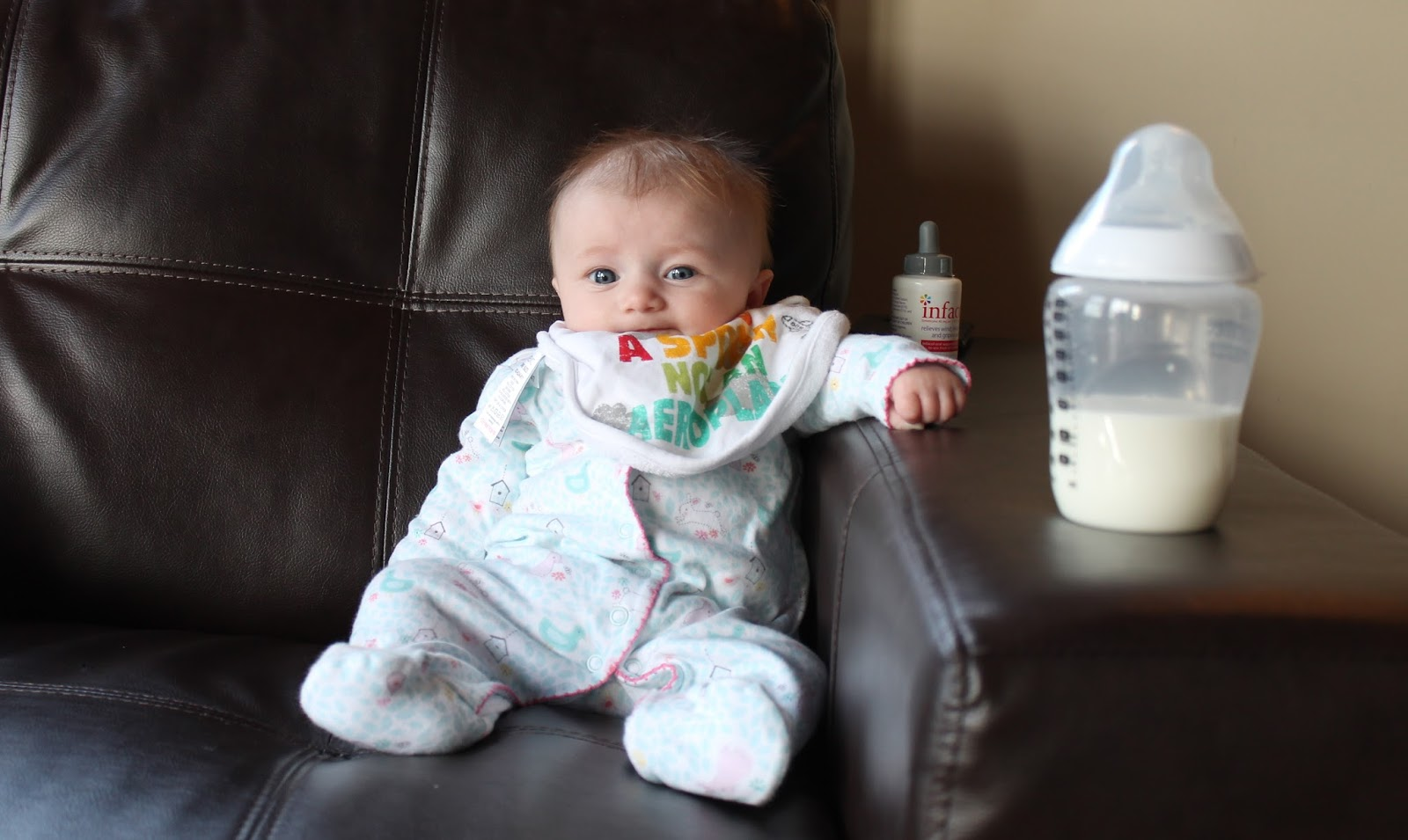 cute baby sitting on sofa with a bottle