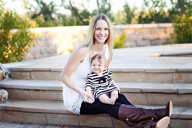 Mom holds baby on cement steps wearing boots