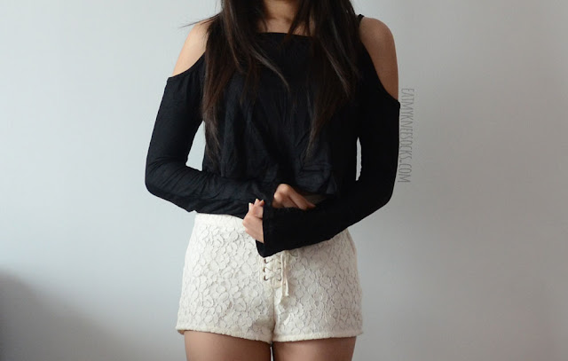 A cute, boho-chic outfit featuring SheIn's black long sleeve cutout cold-shoulder crop top and cream-colored high-waisted lace-up front lace H&M shorts.