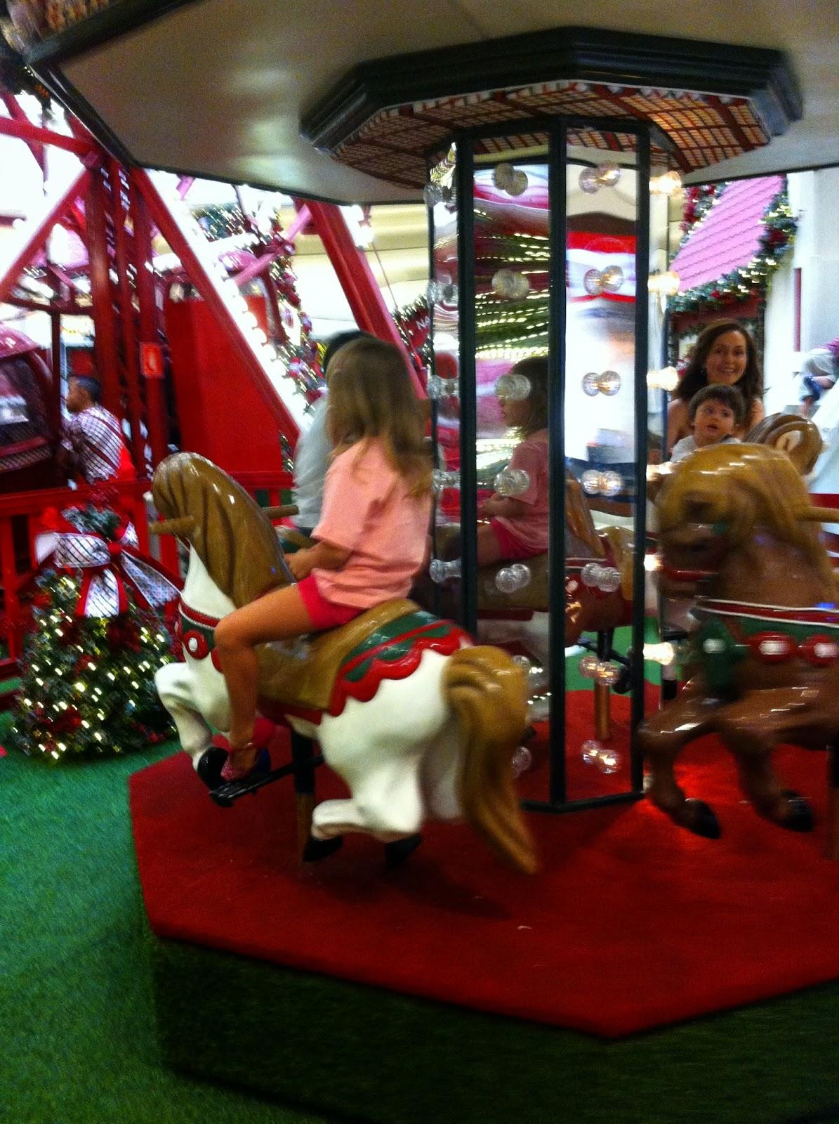 Descrição da Foto: Um carrossel composto por quatro cavalos de brinquedo, espelho e luzes no mastro. As crianças estão sentadas. Estou de pé no fundo acompanhando meu filho.