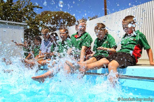 L-R from centre: Rhyzia Nathan, Isobel Lloyd, Amber Fisher, Antony Valdez, pupils at Pakowhai School, Pakowhai, Hawke's Bay, playing in their still-filling newly-painted swimming pool. photograph