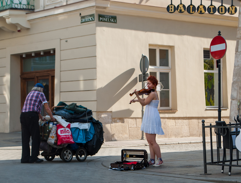 Girl playing the violin and a male worker Kraków, Poland