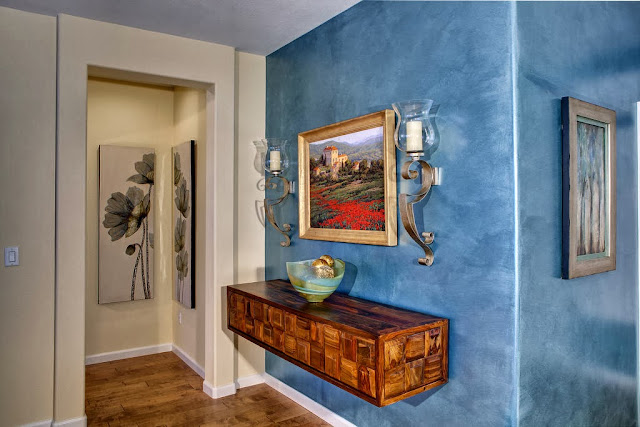 desirable entryway with classic candle holders and dcenery painting