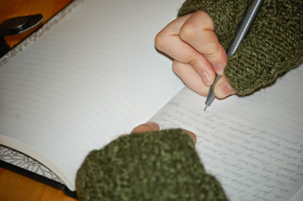 writing with a pen in a journal