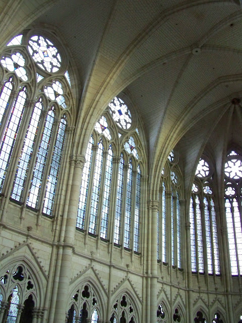 Here you can see an example of the clerestory windows at the Amiens Cathedral in France. Note the vaulted and ribbed pointed arches of the ceiling and how the weight is distributed to supporting columns thus allowing for thinner exterior walls. This photo only: WikiMedia.org.
