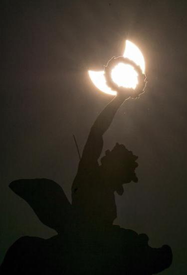 Частичное солнечное затмение на фоне статуи на крыше из дворца Хофбург в Вене, Австрия.