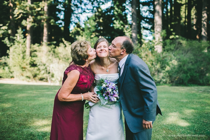 """""""mom and dad kissing bride on the cheek"""""""
