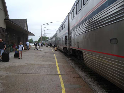 Silver Amtrak train with red, white and blue stripes at a train station
