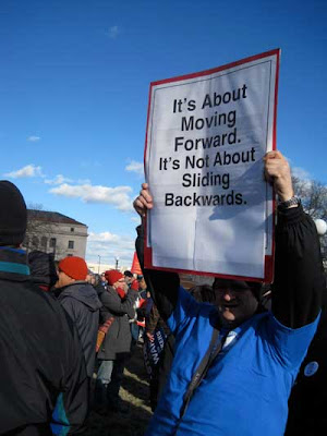 Man with sign reading It's about moving forward, not sliding backward