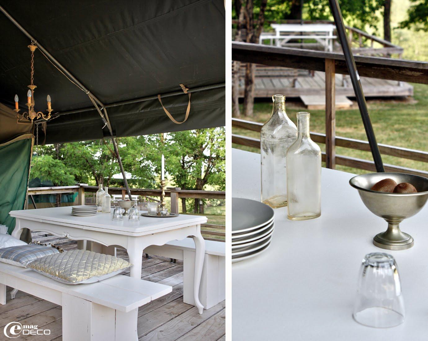 Sur la terrasse en bois d'une tente familiale, une table chinée a été repeinte
