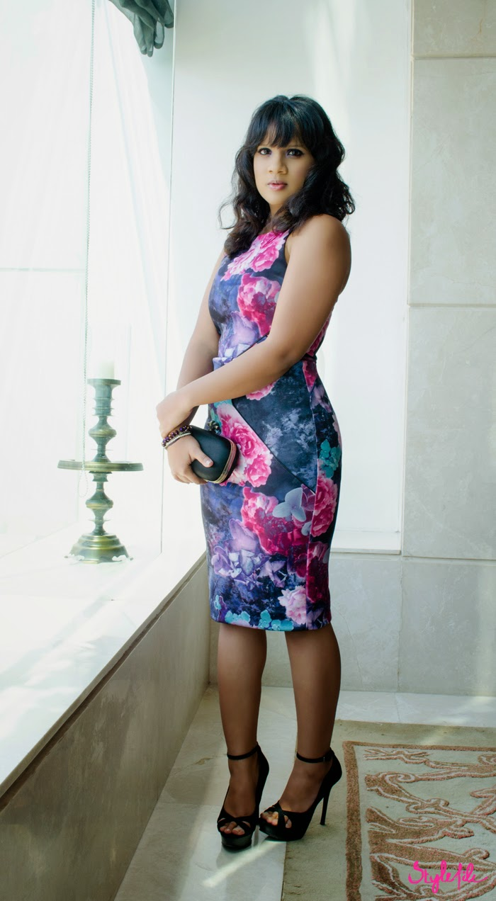 Dayle Pereira of Style File India wears a Miss Selfridge floral print bodycon dress via Jabong paired with Zara stilettos and Accessorize bracelets standing against a glass window
