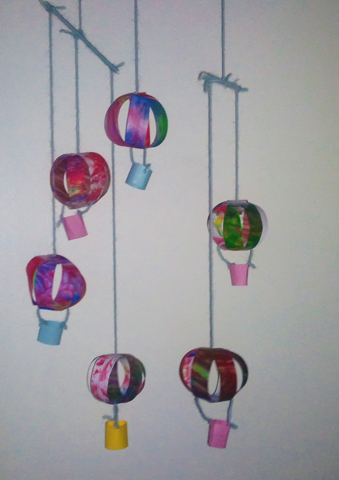 hang a short dowel from each end of the long dowel from each end of the short dowels hang one balloon on one of the short dowels hang the last balloon in