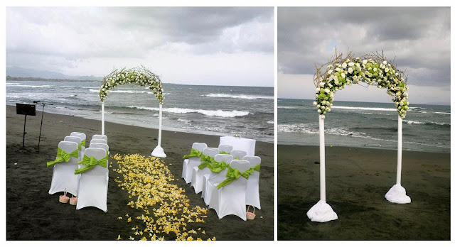 arch made from white bamboo pole and flower mixtures of white roses, green hydrangeas, ruscus leaves and twigs