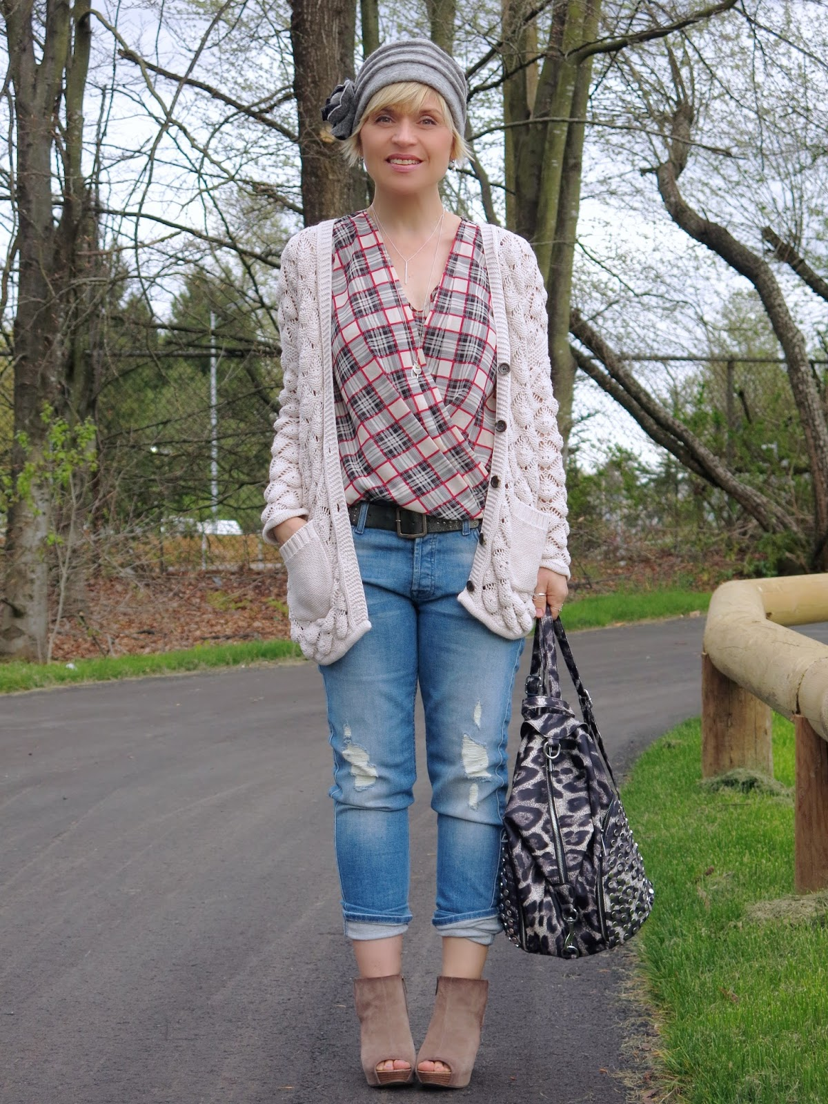 boyfriend jeans styled with a plaid shirt, grandpa cardigan, and felt-flower hat