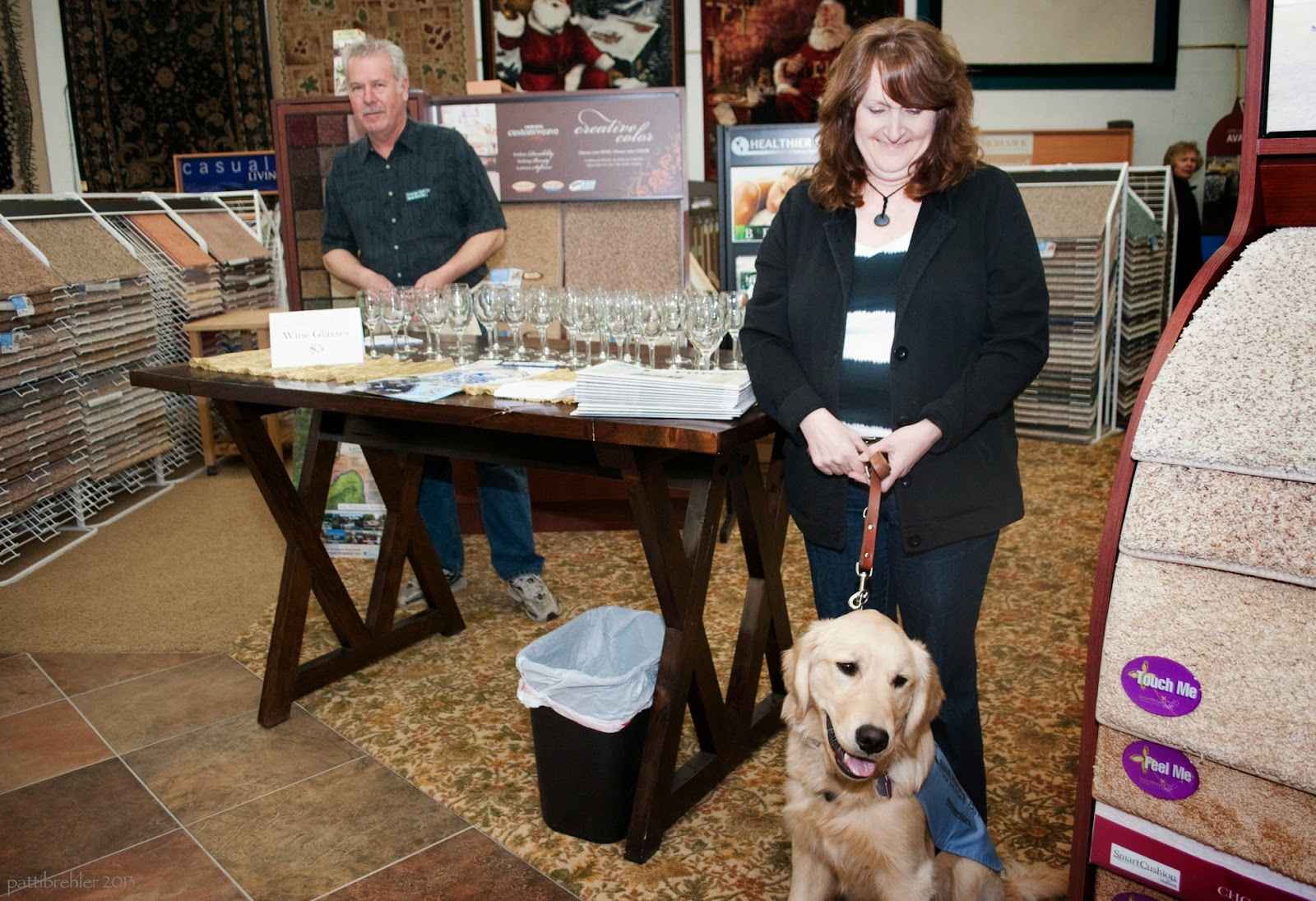 A man wearing a green shirt and blue jeans is standing behind a table that has wine glasses on it. A woman is standing on the right side of the table, she is wearing a black jacket with a black and white striped shirt under it and blue jeans. She has long brown hair and is looking down at a golden retriever that is sitting in front of her. She is holding the dog's brown leash. The dog is wearing a baby blue working jacket. They are all inside of a carpet store, so there are carpet displays on either side of them and behind them.