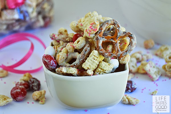 Valentine's Day Snack Mix is a delicious way to share the love with all of your favorite Valentines. This sweet snack mix is made with M&M's® Red Velvet candies, crispy cereal, crunchy pretzels, and salty peanuts all covered in creamilicious white chocolate and sparkly pink sprinkles! #RedVelvetLove #ad