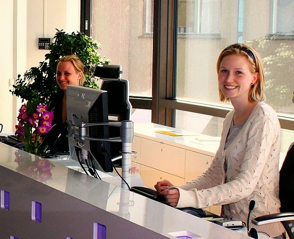 A receptionist sitting behind an office in a workplace.