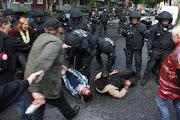 4 Demonstranten sitzen auf der Straße. Einer wird von einem Polizisten