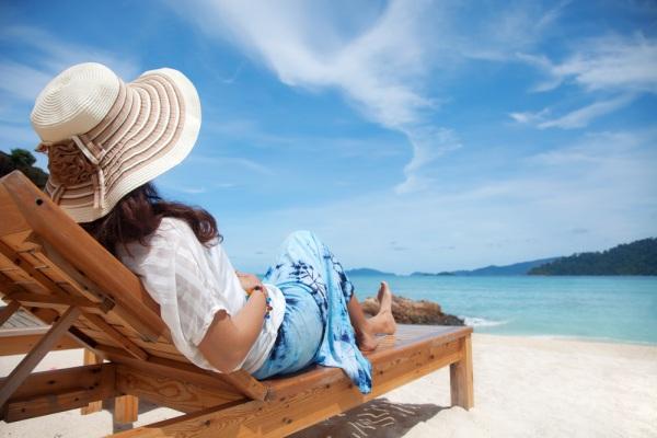 Žena sedi na ležaljci na plaži i uživa u pogedu na more