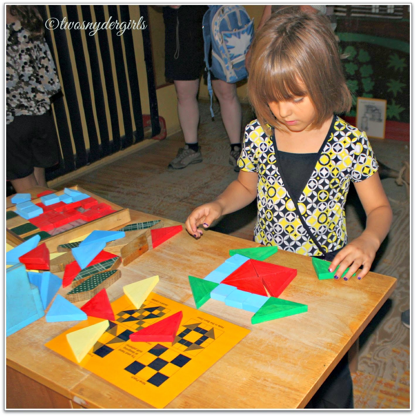 child putting together a wooden math puzzle