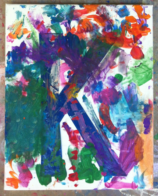 """canvas with the letter """"K"""" taped off mostly covered in random paints"""