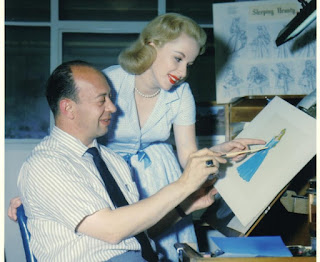 Marc Davis showing a young lady a dress concept for Sleeping Beauty