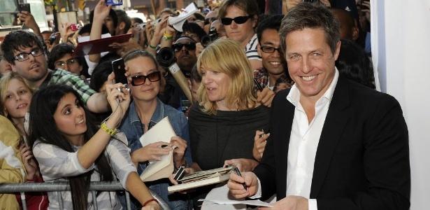 O ator Hugh Grant distribui autógrafos ao chegar no Festival de Toronto para a pré-estreia do filme 'Cloud Atlas' (Foto: AP)
