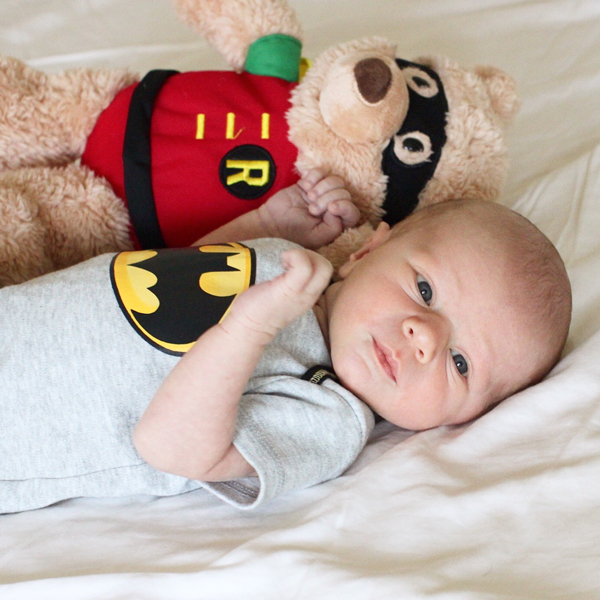 Newborn baby Batman onesie and Robin stuffed animal