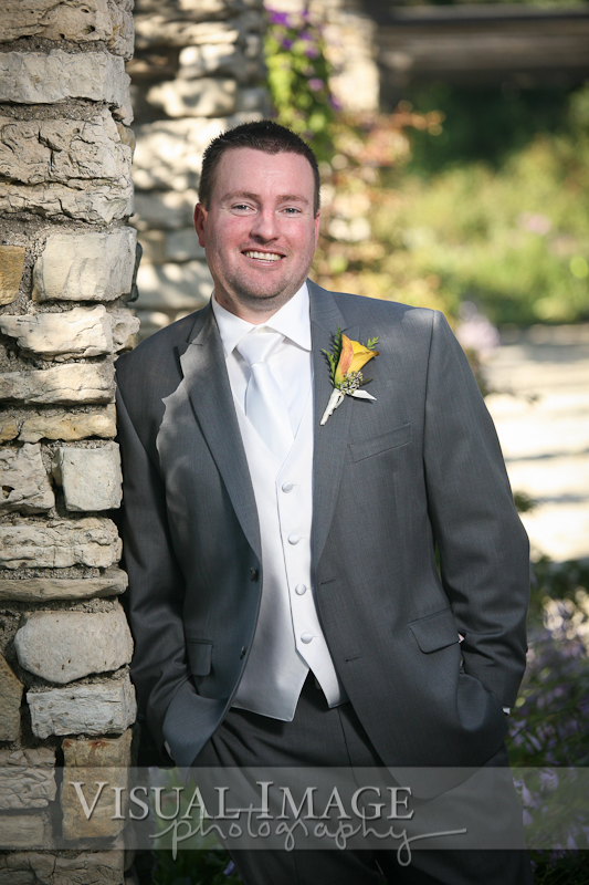 Portrait of groom leaning on rock column in Frame Park