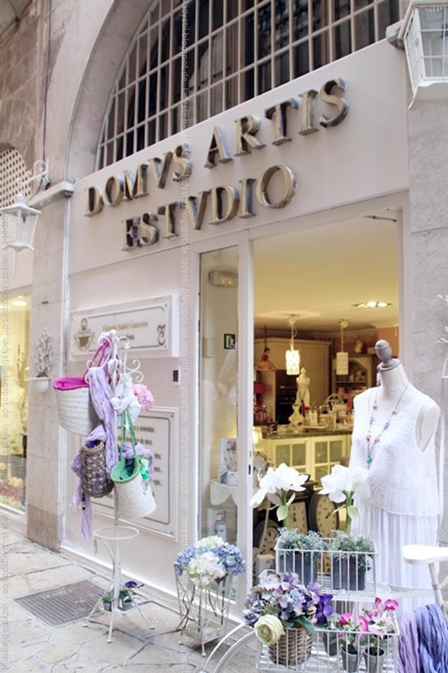 Blickk auf den Eingang des Interior Geschäfts Artis Domvs in Palma mit Ständer voller Korbtaschen
