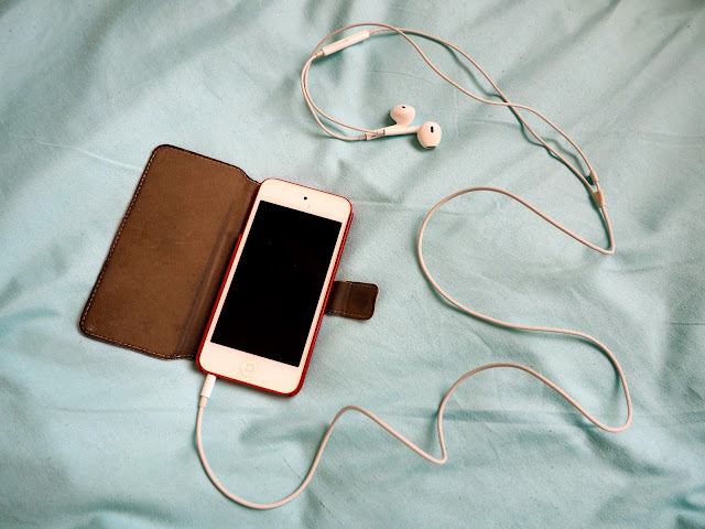 Red 5th generation iPod touch, in red leather flip case, with white headphones