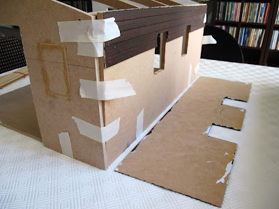 A half-built dolls' house shed, with weatherboard cladding fallen off the rear wall.