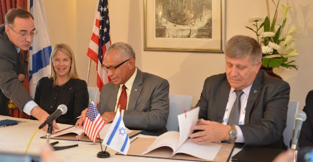 NASA Administrator Charles Bolden (center) and Israel Space Agency Director General Menachem Kidron (right) sign cooperation agreement at the International Astronautical Congress held in Jerusalem, Oct. 13, 2015. Photo Credit: Yair Zrika