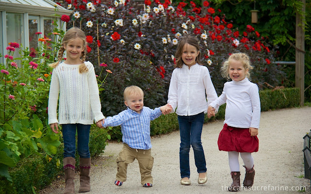 Grandchildren in Bishop's Park Garden in London with colorful flowers in the background.