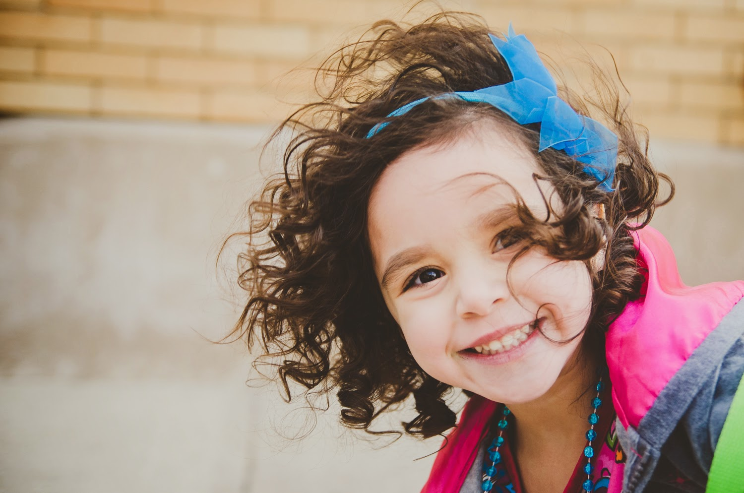 child smiles and looks cute in portraits by child photographer in indianapolis