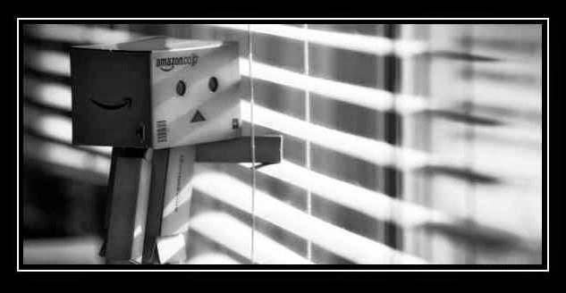 Pequeño muñeco humanizado hecho de cajas que mira melancólico a través de unas persianas.