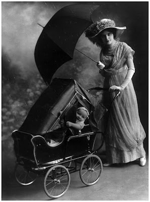Woman, holding umbrella, pushing baby in carriage equipped with rain cover. 1913
