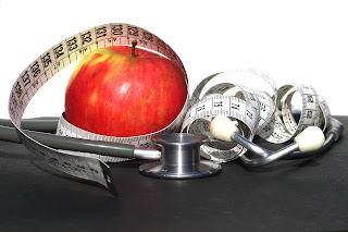 Apple, stethoscope and tape measure