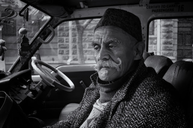 A man with an impressive moustache waits in a minibus taxi outside Cape Town City Hall in this street photograph