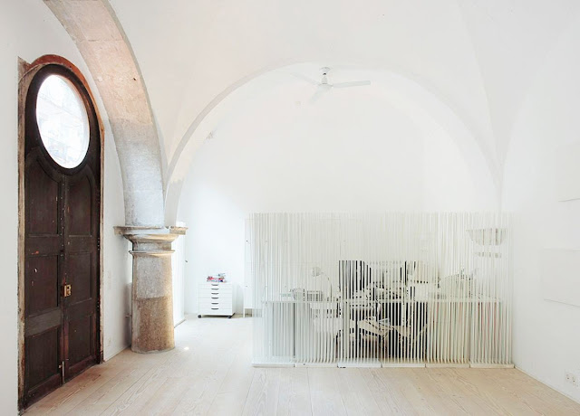 cloister in Barcelona turned into a living room with screen dividers to separate the office from the rest of the room