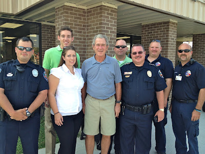 Ph.D. Intern Andrea Weiss poses with President George Bush, local police and other interns during a recent visit to Huntsville.
